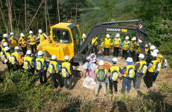한국전력공사가 밀양 송전탑 공사를 재개한지 사흘째인 22일 주민들이 공사 저지를 위해 중장비 쪽에 앉아 있다. 사진은 한국전력 직원들이 주민들을 에워싸고 있는 모습.