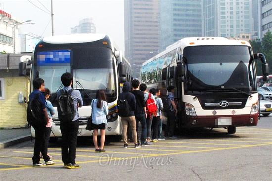 24일 오전 서울역광장에서 국정원 안보교육 참가자들이 국정원이 준비한 버스에 줄지어 탑승하고 있다.