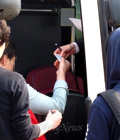 24일 오전 국정원 안보교육 참가자들이 버스에 타면서 국정원 직원에게 신분증을 보여주고 있다.
