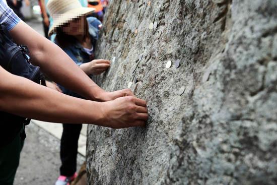 소원 여행자들이 바위에 동전을 붙이고 있다. 무슨 소원으로 동전을 바위에 붙일까 궁금하다.