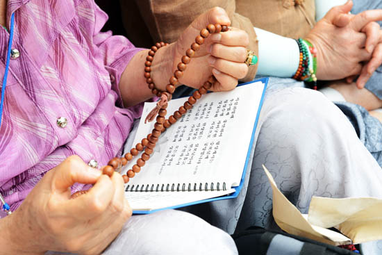 불심 한 할머니가 두 손에 염주를 든 채, 경내 방송에 따라 법화경을 독송하고 있다.