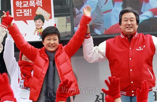 박근혜 새누리당 대선후보가 지난해 11월 30일 오전 부산 사상구 서부버스터미널 유세에서 김무성 총괄선대본부장과 함께 유권자들을 향해 손을 들어 인사하고 있다.