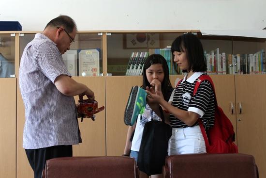 방학을 맞아 모교에 담임선생님을 찾아 온 중학생들이 교장실에 들렀습니다. 김종인 교장선생님이 제자들에게 사탕을 나눠주고 있습니다.