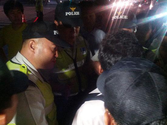 25일 저녁 11시경 집회에 참가했던 한 시민이 경찰과 실랑이를 벌이고 있다.
