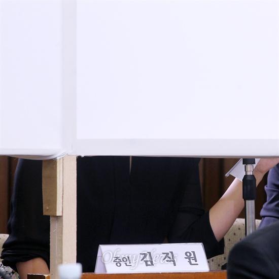 19일 오후 국회에서 열린 국정원 댓글 의혹 사건 등의 진상규명을 위한 국정조사 청문회에 증인으로 출석한 현직 국정원 직원 김하영씨가 흰색 가림막 뒤에 몸을 숨긴 채 증인심문에 응하고 있다. 심문 내내 김씨는 미리 준비해 온 자료를 들고 답변하는 모습을 보였다.