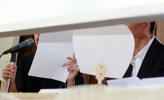 가림막 뒤에서 얼굴 가리고 답변하는 김하영  국정원 직원 김하영씨(왼쪽)가 19일 오후 국회에서 열린 국정원 댓글 의혹 사건 등의 진상규명을 위한 국정조사 청문회에 증인으로 출석해 가림막 뒤에서 미리 준비해 온 답변자료를 들고, 심문에 응하고 있다.