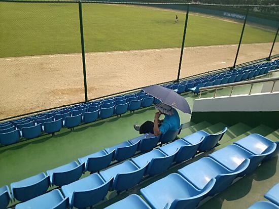 경산볼파크의 텅 빈 1루 관중석. 32도를 웃도는 더운 날씨에 한 관중이 우산을 쓰고 야구를 보고 있다.