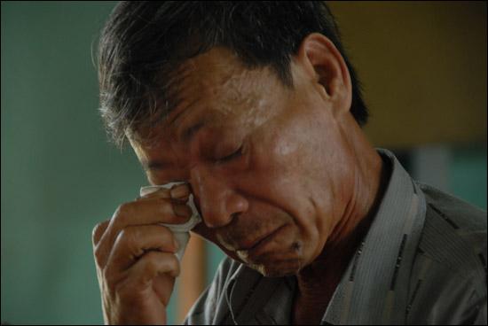 베트남 전쟁 때 한국군이 던진 수류탄에 맞아 불구가 된 '런' 아저씨가 증언을 하며 눈물을 흘리고 있다.