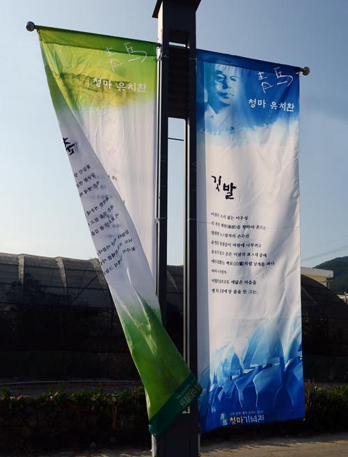 깃발 코스모스 꽃길이 끝나는 지점에 청마의 시 '깃발'이 새겨진 깃발이 바람에 나부끼고 있다.
