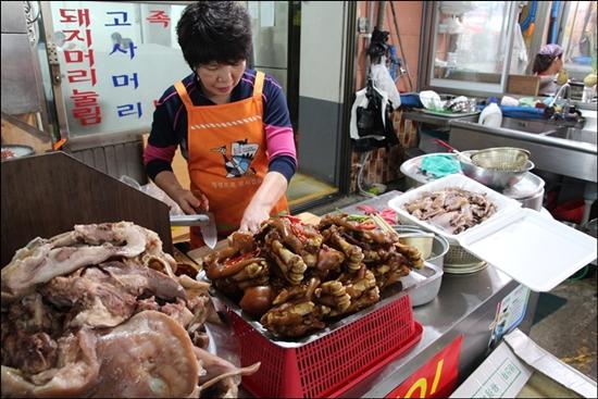 한우식당 주인아주머가 국밥에 넣을 돼지고기를 손질하고 있다.
