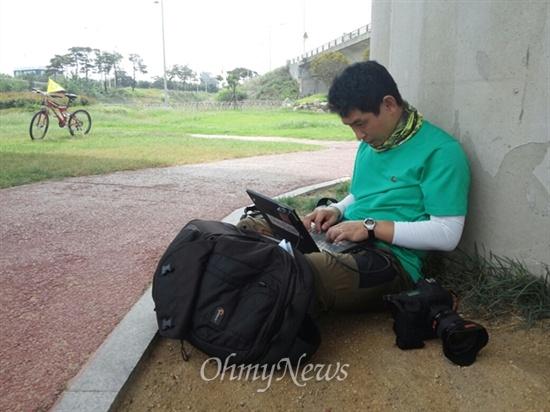 <오마이뉴스> 사진팀 유성호 기자가 낙동대교 밑에서 사진 편집을 하고 있습니다. 유 기자는 큰 카메라와 묵직한 가방을 메고 거침없이 낙동강을 누비고 있습니다