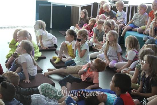 교실에 모여 함께 비디오를 보는 학생들. 누워있기도 하고 자유롭다.