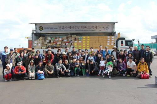 18일 제주항에 도착한 '강정 책마을 십만대권 프로젝트' 참가자들이 3만 5,000여권의 책과 함께 기념사진을 찍었다.