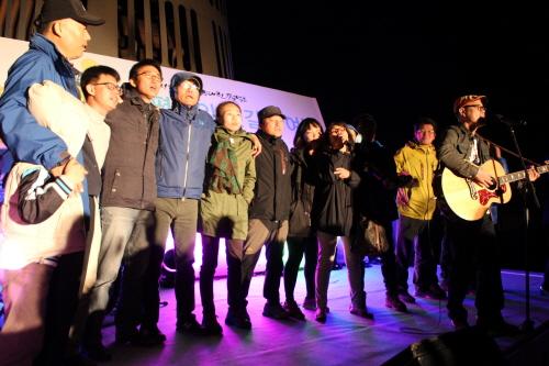 17일 저녁 '강정, 평화책마을 기원 선상 문화제' 말미에 포크 민중가수 손병휘씨와 함께 참가자들이 어깨동무를 하며 '광야에서'를 함께 불렀다.