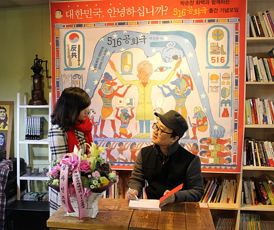 <5·16 공화국> 출판기념회 박순찬 화백이 출판기념회에 참석한 이들에게 사인이 담긴 책을 주고 있다.