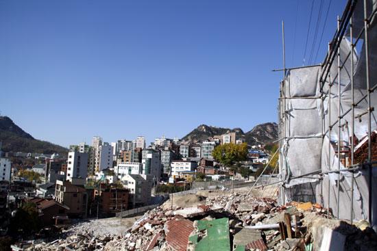 철거 공사가 한창인 돈의문뉴타운 지구 멀리 보이는 아파트들이 파괴된 동네의 미래 모습이다.