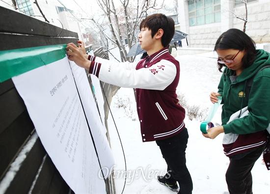 한 고려대 학생이 사회문제에 대한 자신의 생각이 담긴 '안녕들하십니까?' 대자보를 14일 서울 성북구 고려대 정경대 후문에 있는 담벼락 위에 부착하고 있다.