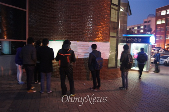 경북대학교 복지관에 붙어 있는 대자보를 지나가던 학생들이 읽고 있다.
