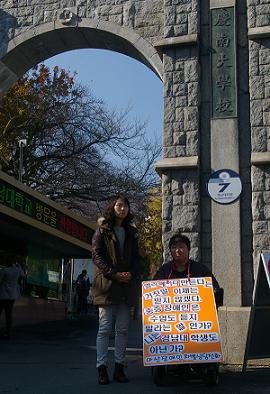 경남대 정문에서 윤종훈씨가 한달이 넘게 엘리베이터 설치를 요구하는 피켓시위를 하고 있다.