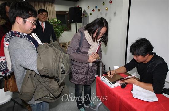 <잃어버린 보온병을 찾아서> 저자 노순택 사진가가 18일 오후 서울 마포구 인권중심 사람 다목적홀에서 열린 저자와의 대화에서 참석자들의 사인 요청이 있자, 직접 책에 사인을 해주고 있다.