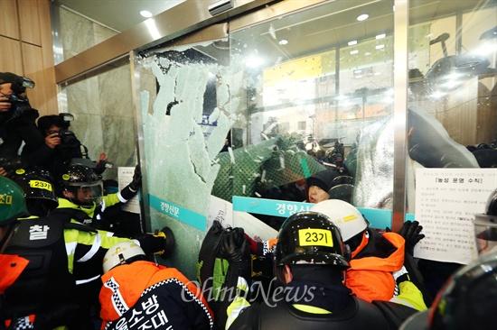 유리깨고 진입하는 경찰병력 민주노총이 입주한 경향신문사 1층 현관 유리문을 열기위해 장비를 든 소방대원들이 투입되어 경찰이 노동자들이 막고 있던 유리문을 깨고 진입을 시도하고 있다.