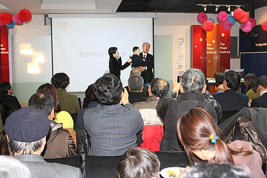 박재승이사장이 최연소 후원자인 원정연(5세)군을 안고 인사말을 하고 있다. 왼쪽은 사회를 맡은 백현욱 교수