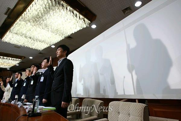 [2013오마이포토] 그림자만 보이는 국정원 핵심 증인들 8월 19일 오전 국정원 댓글 의혹 사건 등을 다루는 국정원 국조특위 청문회에 출석한 국정원 박원동 전 국익정보국장과 김하영씨가 다른 증인들과는 달리 가림막 뒤에서 증인선서를 하고 있다.