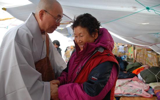 법륜 스님이 고 유한숙 어르신의 분향소를 지키던 고정마을 대봉댁(76)의 손을 잡고 위로하고 있다.