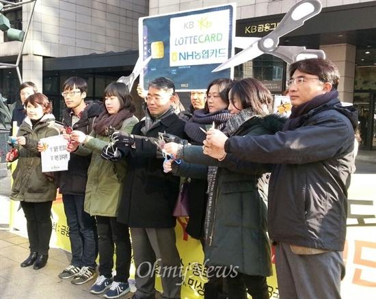 금융정의연대, 에듀머니 등 시민단체 회원들이 27일 오전 서울 종로구 내수동 국민카드 본사 앞에서 카드를 자르기 퍼포먼스를 하고 있다.