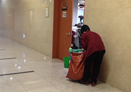 국회 정론관 앞에서 쓰레기통을 비우고 있는 국회 청소노동자