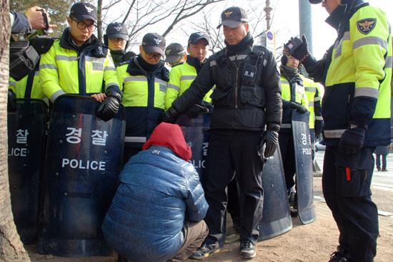 할머니 한 분이 경찰에 포위된 주민을 만나게 해달라고 요구하다 지쳐서 경찰의 다리 밑으로 들어가 보려고 한다.