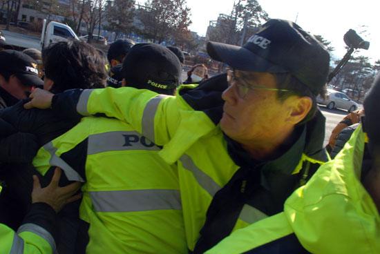 돗자리 하나를 빼앗기 위해 경찰이 주민의 옷을 잡아끌고 있다.