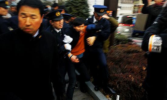 일본 경찰이 2·8도쿄원정대 참가자 가운데 한 명을 버스 안으로 연행하고 있다.