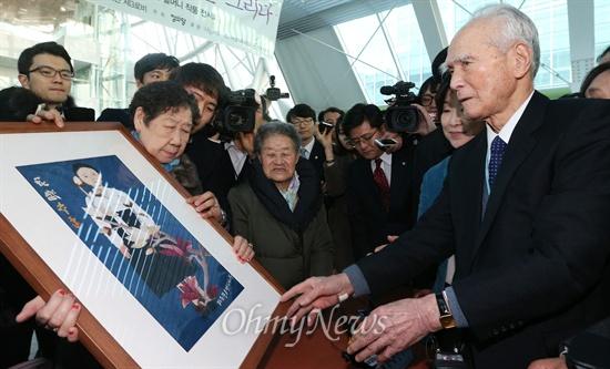 """2박3일의 일정으로 한국을 찾은 무라야마 도미이치(村山 富市) 전 일본 총리가 11일 오후 서울 여의도 국회의사당 의원회관에서 개막한 일본군 위안부 피해자 할머니 작품 전시회 '할머니의 이름으로 평화를 그리다' 전시장을 방문, 강일출 할머니로부터 '못다 핀 꽃'(김순덕 할머니作) 액자를 선물받고 있다.  1990년대 중반 81대 일본 총리를 지낸 무라야마 전 총리는 2차 세계대전 종전 50주년 기념일 당시 """"식민지 지배와 침략으로 아시아 제국의 여러분에게 많은 손해와 고통을 줬다. 의심할 여지없는 역사적 사실을 겸허하게 받아들여 통절한 반성의 뜻을 표하며 진심으로 사죄한다""""는 취지의 '무라야마 담화'를 발표한 바 있다."""
