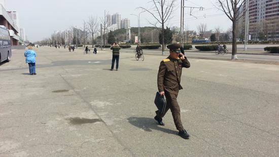 휴대폰 통화하며 평양거리를 걸어가는 군인.
