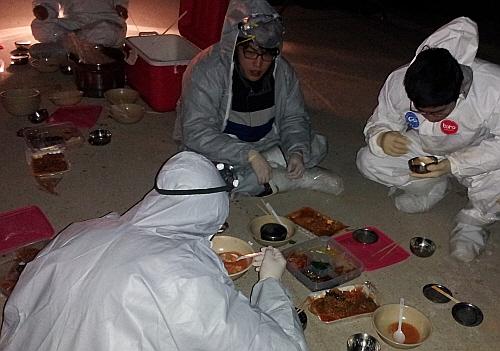 살처분에 투입된 공무원들이 찬 바닥에 앉아 식사를 하고 있다.