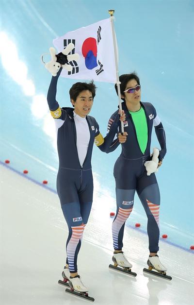 한국 남자 스피드스케이팅의 이승훈과 주형준이 22일 러시아 소치의 아들레르 아레나에서 열린 2014 소치 동계올림픽 스피드스케이팅 남자 팀 추월 결승에서 네덜란드에 이어 은메달을 차지한 뒤 태극기를 들고 관중에게 인사하고 있다.