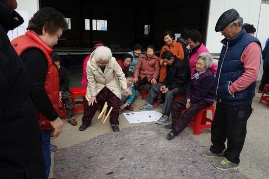 두곡리 마을 주민들이 마을 회관에 모여 윷놀이를 합니다.