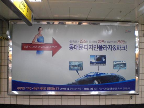 서울 시청역에 설치된 DDP 홍보판 DDP가 건설되면 생산 유발 효과 23조원, 일자리 창출 20만명, 외국인 관광객 280만명이 유치될 것이라는 오세훈 시장 시절의 DDP 홍보판. 2008년 9월 서울시청역에서 촬영했다.