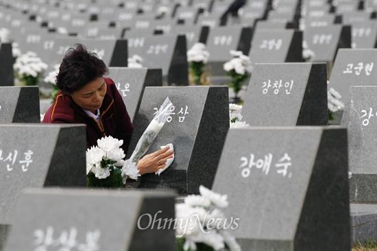 묘비 닦는 4.3희생자 유가족 한 유가족이 3일 오전 제주 4.3희생자 평화공원 제주지역 행방불명희생자 위령비 묘역에서 가족의 묘비를 닦고 있다.