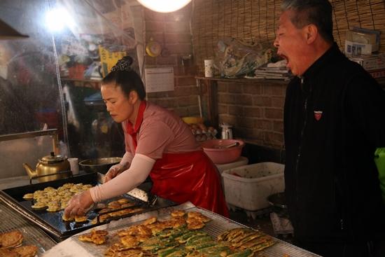 권옥희씨가 동그랑땡을 굽는 것을 지켜보던 남편 박철신씨가 하품을 하고 있다.