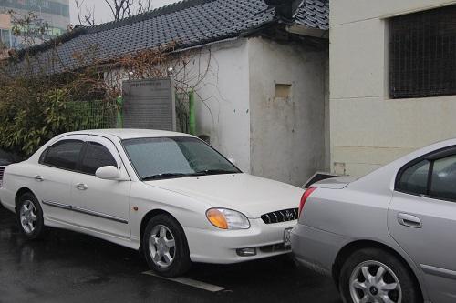 석정 윤세주 생가터 석정 윤세주의 생가임을 알리는 표지판과 표석이 주차된 자동차에 가려져있다.