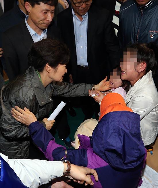 실종자 가족 위로하는 박 대통령  박근혜 대통령이 17일 오후 진도 앞바다에 침몰한 여객선 '세월호' 사고의 실종자 가족이 모여 있는 진도체육관을 방문, 부모가 모두 실종된 한 어린이의 뺨을 어루만지며 위로하고 있다.