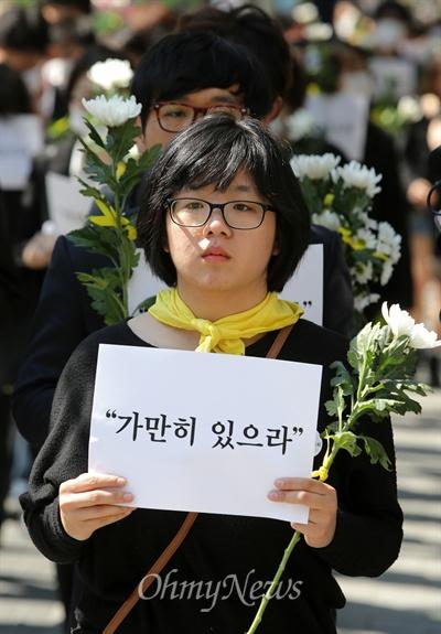 """""""가만히 있을 수 없다"""" 세월호 참사 희생자 추모와 무책임한 정부를 규탄하는 시민들이 3일 오후 마포구 홍대입구역 부근에서 '가만히 있으라'가 적힌 손피켓과 국화꽃을 들고 침묵시위를 벌이고 있다. 이 시위를 제안한 용혜인씨(경희대 정경대 3, 사진)를 비롯한 참석자들은 """"권력자와 기득권자들이 가만히 있으라고 말하는 것을 따를 수 없다""""며 """"가만히 있으면 안된다""""는 뜻을 알리기위해 '가만히 있으라'는 구호를 들고 나왔다고 밝혔다."""