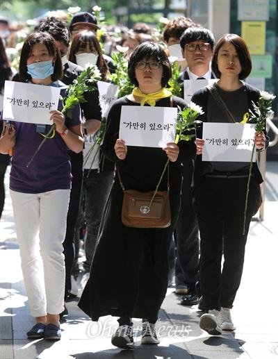 """""""가만히 있을 수 없다"""" 세월호 참사 희생자 추모와 무책임한 정부를 규탄하는 시민들이 3일 오후 마포구 홍대입구역 부근에서 '가만히 있으라'가 적힌 손피켓과 국화꽃을 들고 침묵시위를 벌이고 있다. 이 시위를 제안한 용혜인씨(경희대 정경대 3, 사진 가운데)를 비롯한 참석자들은 """"권력자와 기득권자들이 가만히 있으라고 말하는 것을 따를 수 없다""""며 """"가만히 있으면 안된다""""는 뜻을 알리기위해 '가만히 있으라'는 구호를 들고 나왔다고 밝혔다."""