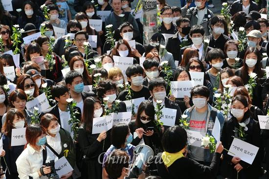 """""""가만히 있을 수 없다"""" 세월호 참사 희생자 추모와 무책임한 정부를 규탄하는 시민들이 3일 오후 마포구 홍대입구역 부근에서 '가만히 있으라'가 적힌 손피켓과 국화꽃을 들고 침묵시위를 벌이고 있다. 이 시위를 제안한 용혜인씨(경희대 정경대 3)를 비롯한 참석자들은 """"권력자와 기득권자들이 가만히 있으라고 말하는 것을 따를 수 없다""""며 """"가만히 있으면 안된다""""는 뜻을 알리기위해 '가만히 있으라'는 구호를 들고 나왔다고 밝혔다."""