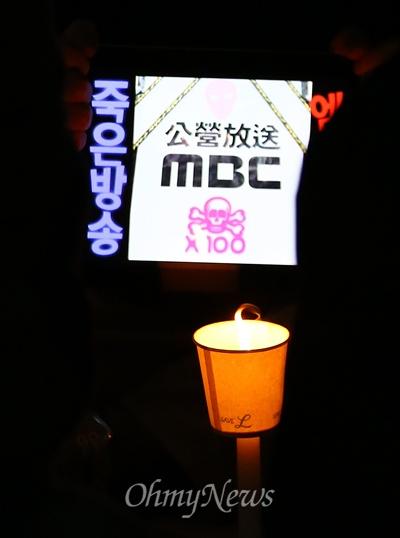 """""""죽은 방송 MBC"""" 7일 오후 서울 여의도 MBC 앞에서 열린 세월호 침몰사고 실종자 무사귀환과 희생자 추모 및 MBC 규탄 국민촛불집회에서 한 참가자가 '죽은방송 MBC'가 적힌 테블릿PC를 촛불과 함께 들고 있다."""