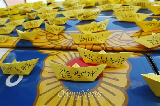 경찰버스 뒤 덮은 종이배 9일 오전 서울 종로구 청운동사무소 앞에서 세월호 유가족과 생존자 가족들이 박근혜 대통령과 면담을 요구하며 전날 밤부터 길거리에 앉아 항의하던 도중 경찰버스에 노란 종이배가 붙어 있다.