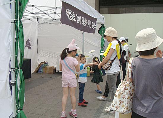 침묵행진 참가자들이 수원역 남측 광장에 도착한 뒤 들고 온 국화를 세월호 참사 희생자 시민분향소에서 희생자들을 추모하는 묵념을 하고 있다.