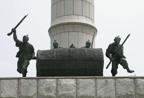 황룡전적지 기념탑에 조각된 동학농민군들. 장태를 굴리며 관군에 맞서는 모습이다.